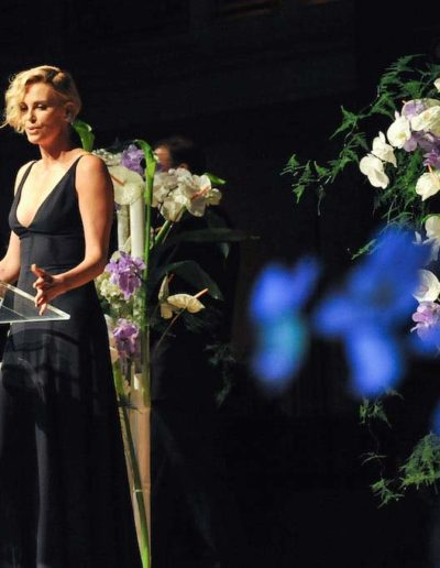 Charlize Theron vor Bühnendekoration bei dem Event Cinema for Peace - ©Fleurop